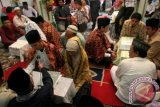 Sejumlah pasangan calon pengantin mengucapkan ijab kabul pada nikah massal se Kecamatan Medan Petisah, Sumut, Sabtu (7/4). Nikah massal yang diikuti 18 pasangan pengantin tersebut, untuk membantu masyarakat mendapatkan legalitas pernikahan sesuai dengan ketentuan yang berlaku. FOTO ANTARA/Irsan Mulyadi1/12