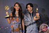 "Aktor Reza Rahadian (kanan) bersama Adinia Wirasti saat menerima penghargaan Indonesia Movie Award 2012 di Tennis Indoor, Senayan, Jakarta, Rabu, (30/5). Reza dan Adinia terpilih sebagai pasangan terbaik dalam film ""Jakarta Maghrib"". FOTO ANTARA/Agus Apriyanto"
