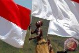 Seorang penari memainkan gerakan atraktif dengan bendera merah putih usai upacara dalam rangka HUT-RI Ke 67 yang berlangsung di Buper, Waena, Jayapura, Papua, Jumat (17/8). Sekitar seribuan lebih pemuda-pemudi terlibat dalam formasi tarian bendera ini. FOTO ANTARA/Anang Budiono