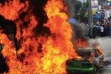 Pekanbaru (Antara Bali) - Sejumlah warga berkerumun di dekat Mobil yang terbakar di Jalan Tuanku Tambusai, Pekanbaru, Riau, Jum'at, (7/9). Kebakaran yang diduga akibat korsleting listrik itu terjadi di jalan Tuanku Tambusai dan menghanguskan sebuah Halte busway tanpa menimbulkan korban jiwa. FOTO ANTARA/Fachrozi Amri/ADT/2012