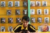 Pekerja menggunakan alat komunikasi dengan latar belakang susunan ponsel di salah satu gerai penjualan ponsel di Jakarta, Jumat (29/3). Data Badan Pusat Statistik (BPS), total impor ponsel Januari 2013 mencapai US$ 219 juta atau sekitar Rp 2,1 triliun dan arus impor perangkat komunikasi ponsel itu terus membengkak. FOTO ANTARA/M Agung Rajasa