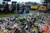 Sejumlah petugas kepolisian dan Muspida Kota Bogor menyaksikan pemusnahan minuman keras dengan cara digilas dengan alat berat di Polres Bogor Kota, Jabar, Senin (15/7). Sedikitnya 5.000 botol minuman keras mengandung alkohol berbagai merek dan satu juta petasan hasil sitaan selama bulan Ramadhan dimusnahkan. ANTARABOGOR/Jafkhairi