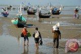 Sejumlah warga berjalan ke arah perahu bermotor, saat akan mudik Idul Adha 1434 H, di Pantai Pagagan, Pademawu, Pamekasan, Jatim, Jumat (11/10). Sejumlah warga Kabupaten Probolinggo, Jatim yang merantau ke Pulau Madura memilih transportasi laut saat akan merayakan Idul Adha bersama keluarga dibanding jalur darat, karena selain ongkosnya jauh lebih murah, jarak tempuh juga lebih singkat. ANTARA FOTO/Saiful Bahri/nym/2013.