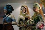 Tiga orang model memperagakan busana pengantin dalam Peragaan Busana pengantin Muslim di Hall MX Mall, Malang, Jawa Timur, Minggu (24/11). Peragaan busana karya para desainer muda tersebut untuk mengenalkan variasi dan kreasi busana pengantin tanpa meninggalkan identitasnya sebagai muslim. ANTARA FOTO/Ari Bowo Sucipto