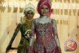 Dua model memperagakan busana pengantin dalam Peragaan Busana pengantin Muslim di Hall MX Mall, Malang, Jawa Timur, Minggu (24/11). Peragaan busana karya para desainer muda tersebut untuk mengenalkan variasi dan kreasi busana pengantin tanpa meninggalkan identitasnya sebagai muslim. ANTARA FOTO/Ari Bowo Sucipto