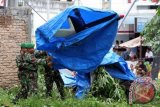 Personel TNI menutup runtuhan helikopter jenis Bell 206 yang jatuh di depan RS Efarina Etaham, Brastagi, Karo, Sumut, Senin (30/12). Akibat peristiwa itu satu orang teknisi heli tewas, dan empat orang lainnya luka. ANTARA FOTO/Irsan Mulyadi/nym/2013.