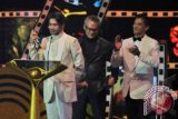 Aktor Reza Rahadian (kiri) memperlihatkan Piala Citra untuk kategori pemeran utama pria terbaik dalam film Habibie & Ainun, pada Malam Penganugerahan Festival Film Indonesia (FFI) 2013 di Marina Convention Centre (MCC) Semarang, Jateng, Sabtu (7/12) malam. ANTARA FOTO/R. Rekotomo
