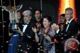 Produser film Sang Kiai Sunil Soraya (kiri) membawa Piala Citra untuk kategori film terbaik, disaksikan Menparekraf Mari Elka Pangestu (tengah) dan Gubernur Jateng Ganjar Pranowo (kanan), pada Malam Penganugerahan Festival Film Indonesia (FFI) 2013 di Marina Convention Centre (MCC) Semarang, Jateng, Sabtu (7/12) malam. ANTARA FOTO/R. Rekotomo