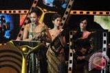 Aktris Adinia Wirasti (kiri) memperlihatkan Piala Citra untuk kategori pemeran utama wanita terbaik dalam film Laura & Marsha, pada Malam Penganugerahan Festival Film Indonesia (FFI) 2013 di Marina Convention Centre (MCC) Semarang, Jateng, Sabtu (7/12) malam. ANTARA FOTO/R. Rekotomo