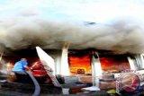 Petugas pemadam kebakaran berusaha memadamkan api yang membakar sebuah toko elektronik di Jln. Sutoyo, Kota Gorontalo, Jumat (14/3). Kebakaran yang belum diketahui penyebabnya itu menghanguskan 2 toko, 1 rumah makan, 1 dealer motor, 1 rumah dan menewaskan satu orang. ANTARA FOTO/Adiwinata Solihin/Asf/Spt/14.