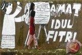 Warga melintas di depan mural bertuliskan Selamat Idul Fitri di kawasan pinggir kali Kanal Banjir Barat, di Jalan Ratu Harhari, Jakarta, Minggu (27/7). ANTARA FOTO/Zabur Karur