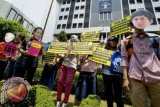 Pegiat anti korupsi yang tergabung dalam Koalisi Masyarakat Sipil Anti Korupsi melakukan aksi dengan menggunakan topeng terpidana kasus korupsi di depan Kantor Kemenkumham Jakarta, Senin (22/9). Aksi yang diikuti puluhan massa itu menuntut Kemenkumham agar menolak seluruh permohonan pembebasan bersyarat yang diajukan oleh terpidana kasus korupsi serta mempublikasikan seluruh pemberian pembebasan bersyarat kepada publik sebagai bentuk pertanggungjawaban moral. ANTARA FOTO/Wahyu Putro A/wdy/14.
