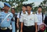Pilot pesawat latih Cessna asal Singapura, Tan Chin Kian (kedua kanan) bersama Xiang Bohong dan Zheng Chen berjalan didampini anggota TNI AU, sebelum terbang dari Lanud Supadio di Kabupaten Kubu Raya, Kalbar, Rabu (29/10). Pesawat latih jenis Cessna asal Singapura dengan tiga kru yaitu Tan Chin Kian (64), Xiang Bohong (25) dan Zheng Chen (24) dipaksa mendarat oleh TNI AU ke Lanud Supadio pada Selasa (28/10) karena tidak memiliki izin terbang di wilayah Indonesia. Mereka telah dibebaskan karena sudah melengkapi sejumlah dokumen izin penerbangan dari Mabes TNI AU dan Dirjen Perhubungan Udara, serta membayar denda sebesar Rp60 Juta sesuai aturan yang berlaku. ANTARA FOTO/Jessica Helena Wuysang