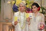 Artis sekaligus presenter Raffi Ahmad (kiri) bersama istri Nagita Slavina (kanan) menunjukan buku nikah seusai akad nikah di Jakarta, Jumat, (17/10). ANTARA FOTO/Julius Wiyanto