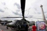 Pengunjung memperhatikan sebuah helikopter milik TNI AD pada Pameran Alat Utama Sistem Persenjataan (Alutsista) TNI AD di Silang Monas, Jakarta, Jumat (12/12). Pameran yang menampilkan 200 jenis peralatan tempur diantaranya persenjataan infanteri, kavaleri, artileri medan dan pertahanan udara itu diselenggarakan dalam rangka memperingati Hari Juang Kartika Ke-69 yang berlangsung pada 12-15 Desember. ANTARA FOTO/Muhammad Adimaja/wdy/14.
