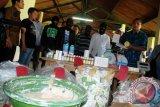 Kasubdit Krimsus Polda Jabar AKBP Eko Sulistyo (kanan) menunjukkan barang bukti produk kosmetik ilegal beserta tersangka di Mapolda Jabar, Bandung, Jabar, Jumat (16/1). Polda Jabar berhasil menangkap empat pelaku beserta ratusan barang bukti farmasi jenis kosmetik bahan berbahaya jenis Merkuri siap edar tanpa ijin produksi dan ijin edar dari BPOM, dengan omzet mencapai ratusan juta/bulan. ANTARA FOTO/Fahrul Jayadiputra/ed/ama/15