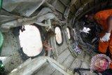 Petugas memeriksa badan pesawat AirAsia QZ8501 di Pelabuhan Tanjung Priok, Jakarta Utara, Senin (2/3). Badan pesawat tersebut selanjutnya diserahkan kepada Komite Nasional Keselamatan Transportasi (KNKT) untuk dilakukan penyelidikan. ANTARA FOTO/Zabur Karuru/pd/15