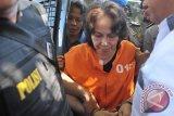 Tersangka kasus pembunuhan Angeline, Margriet Megawe (tengah) digiring polisi saat mengikuti rekonstruksi di rumahnya di Denpasar, Senin (6/7). Margriet bersama mantan pembantunya, Agus yang juga menjadi tersangka dalam kasus itu, menjalani 81 adegan dalam rekonstruksi pembunuhan terhadap anak angkatnya, Angeline Megawe (8 tahun) yang sebelumnya sempat dilaporkan hilang. ANTARA FOTO/Nyoman Budhiana/i018/2015.