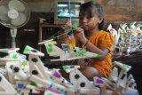 Perajin memasang bendera pada tiap kapal gabus pesanan di kediamannya di Kecamatan Seberang Ulu I Palembang, Sumsel, Jumat (31/7). Kapal Gabus merupakan tradisi musiman yang dijual hanya pada saat dan menjelang perayaan HUT RI di jalanan Kota Palembang, umumnya disandingkan dengan telur bercangkang merah atau dikenal dengan telok abang. ANTARA FOTO/ Feny Selly/ss/pd/15