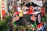 Presiden Joko Widodo (kedua kiri) didampingi Gubernur Kalbar Cornelis (kedua kanan), dan musisi Abdee Negara (kiri), menyapa warga saat mengikuti parade mobil hias Karnaval Khatulistiwa di Pontianak, Sabtu (22/8). Karnaval Khatulistiwa yang digelar untuk memperingati HUT ke-70 RI tersebut dimeriahkan dengan sejumlah acara budaya. ANTARA FOTO/Jessica Helena Wuysang/kye/15