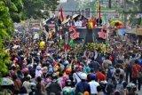 Presiden Joko Widodo (kiri) didampingi Ibu Negara Iriana Joko Widodo (kedua kiri) serta Gubernur Kalbar Cornelis (kanan) menyapa warga saat berpawai dalam rangkaian Karnaval Khatulistiwa 2015 di Jalan Teuku Umar, Pontianak, Kalimantan Barat, Sabtu (22/8). Karnaval Khatulistiwa 2015 dalam rangka puncak peringatan HUT ke-70 Kemerdekaan RI diikuti 24 Propinsi yang terdiri dari karnaval darat 4075 orang, karnaval air 1535 orang, mobil hias 145 armada, kapal hias 251 armada, 100 sepeda ontel hias, dan 50 motor hias. ANTARA FOTO/Yudhi Mahatma/kye/15