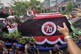 Presiden Joko Widodo (kiri) bersama Gubernur Kalbar Cornelis (kanan), serta musisi Abdee Slank (tengah) menyapa warga saat berpawai dalam rangkaian Karnaval Khatulistiwa 2015 di Jalan Teuku Umar, Pontianak, Kalimantan Barat, Sabtu (22/8). Karnaval Khatulistiwa 2015 dalam rangka puncak peringatan HUT ke-70 Kemerdekaan RI diikuti 24 Propinsi yang terdiri dari karnaval darat 4075 orang, karnaval air 1535 orang, mobil hias 145 armada, kapal hias 251 armada, 100 sepeda ontel hias, dan 50 motor hias. ANTARA FOTO/Yudhi Mahatma/kye/15