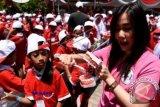Seorang mahasiswi memberikan instruksi cara menggosok gigi yang benar disela peresmian Bulan Kesehatan Gigi Nasional (BKGN) 2015 di Fakultas Kedokteran Gigi Universitas Airlangga (Unair) Surabaya, Jawa Timur, Rabu (16/9). BKGN yang diikuti sekitar 500 siswa sekolah dasar tersebut bertujuan untuk mengajarkan cara menggosok gigi yang benar sejak dini. ANTARA FOTO/M Risyal Hidayat/wdy/5