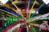 Seorang warga memegang hiasan Bunga Manggar yang akan dipasang di depan rumah, di Pontianak, Kalbar, Rabu (21/10). Pemerintah Kota Pontianak menghimbau kepada masyarakat Pontianak untuk memasang hiasan khas Melayu berupa Bunga Manggar di setiap kantor instansi negara, kantor swasta dan perumahan, untuk menyambut hari jadi Pontianak ke-244 pada Jumat (23/10). ANTARA FOTO/Jessica Helena Wuysang/15