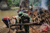 Satgas Banjir dari Dinas Bina Marga dan Sumber Daya Air Kota Depok bersama anggota Kodim 0508 membersihkan tumpukan sampah dan material kayu yang menghambat aliran sungai Ciliwung di bawah Jembatan Panus, Depok, Jawa Barat, Kamis (12/11). Kegiatan bersih ciliwung tersebut dilakukan untuk memperlancar aliran sungai sebagai upaya mencegah banjir memasuki musim hujan. (ANTARA FOTO/Indrianto Eko Suwarso)