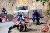 Beberapa ojek membawa kotak suara yang akan didistribusikan ke daerah terpencil di kecamatan Lindu, Sigi, Sulawesi Tengah, Senin (7/12). KPUD Sigi mendistibusikan 32 kotak suara untuk daerah terpencil yaitu Desa Tomado, Anca, Puro\'o, dan Langko. (ANTARA FOTO/Fiqman Sunandar)
