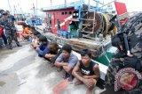 Anggota Ditjen Pengawasan Sumber Daya Kelautan dan Perikanan (PSDKP) Batam menjaga 13 awak kapal beserta tiga kapal nelayan asing asal Malaysia yang ditangkap bersama 13 awak kapal di Batam, Kepulauan Riau, Senin (7/3). Ketiga kapal tersebut KM SLFA 4625, KM KHF1917 dan KM PKFB1512 ditangkap di Perairan Selat Malaka dengan menggunakan Kapal Patroli (KP) Hiu 3215 karena mencuri ikan dengan menggunakan pukat harimau (trawl). (Foto M N Kanwa)