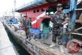 Anggota Ditjen Pengawasan Sumber Daya Kelautan dan Perikanan (PSDKP) Batam menjaga tiga kapal nelayan asing asal Malaysia yang ditangkap bersama 13 awak kapal di Batam, Kepulauan Riau, Senin (7/3). Ketiga kapal tersebut KM SLFA 4625, KM KHF1917 dan KM PKFB1512 ditangkap di Perairan Selat Malaka dengan menggunakan Kapal Patroli (KP) Hiu 3215 karena mencuri ikan dengan menggunakan pukat harimau (trawl). (Foto M N Kanwa)
