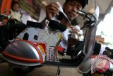 Perajin menyelesaikan pembuatan miniatur motor Vespa berbahan baku utama dari kaleng bekas minuman ringan di Kelurahan Blabak, Kota Kediri, Jawa Timur, Sabtu (23/4). Kerajinan tangan seharga Rp35.000 - Rp100.000 per buah yang memanfaatkan sejumlah limbah tersebut banyak diburu oleh kolektor dari Jakarta dan Surabaya. Antara Jatim/Prasetia Fauzani/zk/16