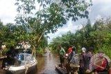 Wakil Bupati Kubu Raya Hermanus, bersama anggota DPRD Kubu Raya Suharso dan unsur muspika Sungai Ambawang menyerahkan bantuan bagi korban banjir di keamatan kuala mandor B (Foto Antara Kalbar/Rendra Oxtora)
