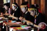 Empat perempuan Dayak merangkai manik-manik kreasi, saat mengikuti lomba anyam manik di Pekan Gawai Dayak ke-31 di Rumah Radakng, Pontianak, Kalbar, Senin (23/5). Anyaman manik-manik yang dapat dikreasikan menjadi dompet, dasi, gelang serta pakaian dengan warna dominan kuning dan merah tersebut, merupakan salah satu kerajinan unggulan etnik Dayak dari Kalbar. FOTO ANTARA/Jessica Helena Wuysang/16
