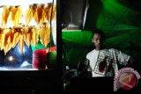 Seorang pedagang membakar Sopang atau Sotong Pangkong yang dijual seharga Rp10 ribu - Rp40 ribu per potong, di Jalan Merdeka Barat, Pontianak, Kalbar, Selasa (14/6) malam. Sopang adalah kuliner khas Pontianak berupa cumi-cumi kering bakar yang dipukul-pukul dengan menggunakan palu, dan dijual hanya pada malam hari selama bulan Ramadan. ANTARA FOTO/Jessica Helena Wuysang/16
