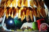 Seorang pedagang menyiapkan Sopang atau Sotong Pangkong yang dijual seharga Rp10 ribu - Rp40 ribu per potong, di Jalan Merdeka Barat, Pontianak, Kalbar, Selasa (14/6) malam. Sopang adalah kuliner khas Pontianak berupa cumi-cumi kering bakar yang dipukul-pukul dengan menggunakan palu, dan dijual hanya pada malam hari selama bulan Ramadan. ANTARA FOTO/Jessica Helena Wuysang/16