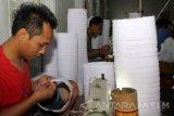 Sejumlah pekerja menyelesaikan pembuatan songkok di Genteng, Banyuwangi, Jawa Timur, Selasa (21/6). Pemilik usaha songkok tersebut mengaku, selama bulan ramadan hasil produksinya menurun sekitar 30 persen karena karyawannya mengganti jam kerjanya dimalam hari untuk menjalankan ibadah puasa. Antara Jatim/ Budi Candra Setya/zk/16.