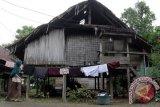 Warga menjemur pakaian di depan rumahnya yang terbuat dari kontruksi kayu berdinding pelepah pohon  rumbia dan bambu , di daerah pedalaman Desa Siron Blang, Kecamatan Kuta Cut Glie, Kabupatren Aceh Besar, Aceh, Rabu (20/7). Puluhan unit rumah warga miskin tidak layak huni di dua desa, gampong Siron Blang dan Gampong Siron Krueng berpenduduk 140 KK itu, selain rumah  tidak layak huni, juga kesulitan air minum dan keseharian mereka mengkonsumsi air sungai untuk diminum dan mencucui serta membutuhkan jembatan permanen untuk transportasi anak sekolah dan perekonomian mereka. ANTARA Aceh/Ampelsa/16