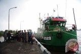 Sejumlah perwira TNI AL bersama Anak Buah Kapal (ABK) berdiri di sebelah kapal berbendera Malaysia hasil tangkapan, di dermaga Mako Lantamal XII Pontianak, Selasa (20/9). Pos TNI Angkatan Laut (Posal) Temajuk yang berada di bawah naungan Lantamal XII Pontianak berhasil menangkap KM SF 1-2929 jenis kapal ikan berbendera Malaysia saat tengah menarik jaring trawl berisi muatan sekitar 750 Kilogram ikan di Perairan Tanjung Datu, Temajuk pada Minggu (18/9). ANTARA FOTO/Jessica Helena Wuysang/16
