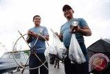 Dua anggota TNI AL memperlihatkan barang bukti berupa alat kemudi dan lampu kapal pencuri ikan berbendera Malaysia hasil tangkapan, di dermaga Mako Lantamal XII Pontianak, Selasa (20/9). Pos TNI Angkatan Laut (Posal) Temajuk yang berada di bawah naungan Lantamal XII Pontianak berhasil menangkap KM SF 1-2929 jenis kapal ikan berbendera Malaysia saat tengah menarik jaring trawl berisi muatan sekitar 750 Kilogram ikan di Perairan Tanjung Datu, Temajuk pada Minggu (18/9). ANTARA FOTO/Jessica Helena Wuysang/16