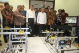 Menteri Riset, Teknologi dan Pendidikan Tinggi (Menristekdikti) Mohamad Nasir (tujuh kanan) didampingi Ketua Dewan Penyantun Politeknik Elektronika Negeri Surabaya (PENS) Mohammad Nuh (ketiga kiri) serta Direktur PENS Zainal Arief (kelima kiri) melihat alat Port-Simulator saat berkunjung ke Surabaya, Jawa Timur, Jumat (28/10). Kunjungan tersebut dalam rangka memantau perkembangan pendidikan vokasi dan inovasi-inovasi teknologi yang telah dibuat untuk mendukung kebutuhan masyarakat dan industri. Antara Jatim/Moch Asim/zk/16