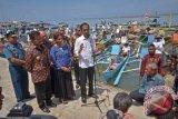 Presiden Joko Widodo (tengah) didampingi Menteri Kelautan dan Perikanan Susi Pujiastuti (ketiga kiri), Gubernur Sulsel, Syahrul Yasin Limpo (kedua kiri) menjawab pertanyaan wartawan usai meresmikan Pelabuhan Perikanan (PP) Untia di Kecamatan Biringkanaya, Makassar, Sulawesi Selatan, Sabtu (26/11). PP Untia menempati lahan seluas 5,4 hektar akan mendukung aktivitas nelayan yang berada di zona Wilayah Pengelolaan Perikanan 731 yang meliputi perairan Flores dan laut Bali yang memiliki potensi sumber daya ikan sebesar 929.700 ton pertahun dan diharapkan dapat meningkatkan produksi perikanan tangkap Sulsel sebagai salah satu penghasil ikan terbesar di Indonesia. ANTARA FOTO/Dewi Fajriani/wdy/16.