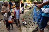 Seekor monyet melakukan antraksi untuk menghibur warga di RTH Kebonrojo, Jombang, Jawa Timur, Sabtu (24/12). Dalam sehari rombongan topeng monyet tersebut mendapatkan penghasilan rata-rata Rp 200 ribu. Antara Jatim/Syaiful Arif/zk/16