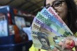 Warga saat menunjukkan uang pecahan baru di kawasan Blok M, Jakarta. Bank Indonesia resmi meluncurkan uang baru sehingga masyarakat dapat menukar uang lamanya maksimal sebesar Rp3.800.000 dengan 100 lembar per pecahan di sejumlah gerai penukaran uang Bank Indonesia di seluruh Indonesia.  (ANTARA FOTO/Muhammad Adimaja/Dok).