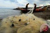 Nelayan tradisional menggulung jaring ikan yang terkena pencemaran minyak di kawasan laut Lhokseumawe, Provinsi Aceh, Selasa (31/1). Nelayan di kawasan itu mengaku aktivitas melaut mereka terhambat oleh minyak yang diduga oli bekas dengan bau menyengat yang mencemari hingga radius 5 kilometer, yang berdampak pada sulitnya mendapatkan tangkapan ikan. (ANTARA FOTO/Rahmad)