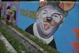 Seorang seniman membuat mural pada tembok yang sebelumnya dipenuhi oleh coret-coretan vandalisme di Palu, Sulawesi Tengah, Sabtu (18/2). Selain dapat memperindah tampilan kota terutama menghilangkan kesan kumuh, karya seni mural yang kaya akan kritikan sosial itu juga bisa menarik wisatawan. ANTARA FOTO/Mohamad Hamzah/pd/17.