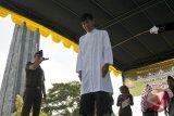 Terpidana warga keturunan Tionghoa (non muslim) menjalani hukuman cambuk di Masjid Agung Al Munawir, Kota Jantho, Kabupaten Aceh Besar, Aceh, Jumat (10/3). Terpidana warga Tionghoa dalam kasus sabung ayam itu memilih hukuman  sebanyak 8 cambuk setelah dipotong masa tahanan satu cambuk, ketimbang hukuman pidana umum. (ANTARA Aceh/Ampelsa)