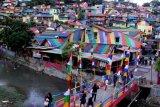 Sejumlah wisatawan saat berwisata mengunjungi Kampung Pelangi Wonosari, Randusari, Semarang, Jawa Tengah, Sabtu (20/5). Kampung yang aslinya bernama Kampung Wonosari itu berada di bukit tengah kota dan terlihat jelas rumah yang dicat warna-warni, sehingga banyak dikunjungi wisatawan serta menjadi destinasi wisata baru dan menjadi sorotan media internasional. ANTARA FOTO/Yulius Satria Wijaya/foc/17.