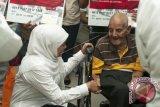 Menteri Sosial Khofifah Indar Parawansa (kiri), menyalami Alfrel Matmey (kanan), lansia berusia 93 tahun penerima Kartu Keluarga Sejahtera, saat pemberian bantuan Paket Keluarga Harapan (PKH) untuk 300 Keluarga Penerima Manfaat (KPM) di Ambon, Maluku, Kamis (25/5). Mensos juga berkesempatan menyerahkan bantuan paket sembako dan alat salat kepada 142 Kepala Keluarga eks-pengungsi korban konflik antarwarga. ANTARA FOTO/Embong Salampessy/kye/17.